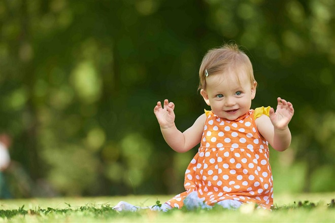bé gái mặc đầm cam ngồi chơi trên bãi cỏ