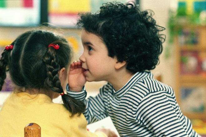 bé trai nói nhỏ vào tai bé gái