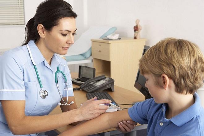 cô y tá tiêm vắc xin cho bé