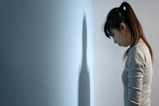 cô gái buồn nhìn vào góc tường