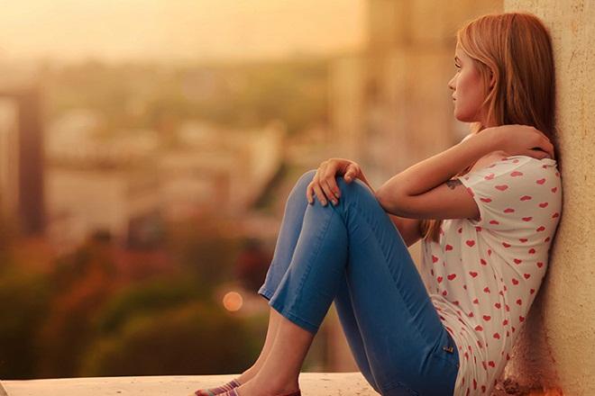 cô gái buồn ngồi dựa vào tường