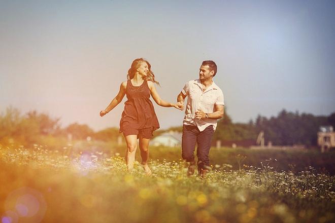đôi tình nhân nắm tay nhau chạy trong vườn hoa