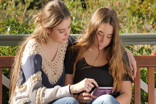 hai người bạn cùng nhau xem điện thoại
