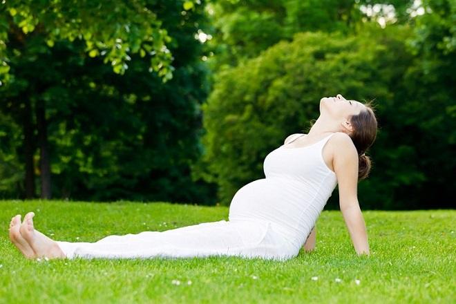 bà bầu khởi động làm nóng cơ thể trước khi tập thể dục với bóng