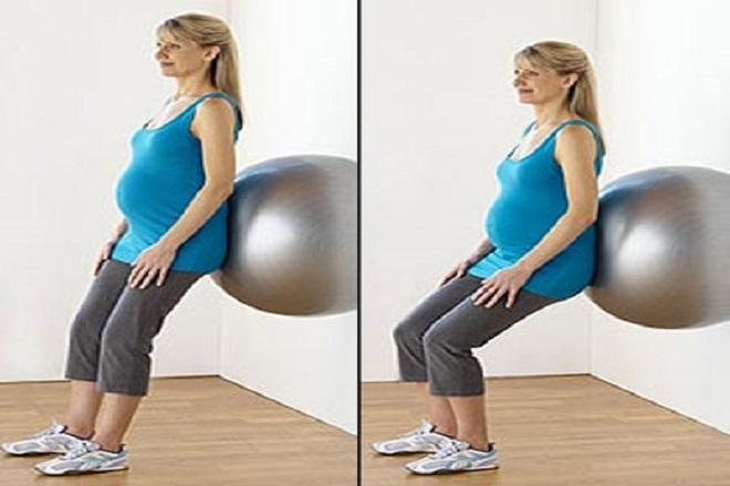 bà bầu tập thể dục với bóng bằng cách dựa lưng vào bóng