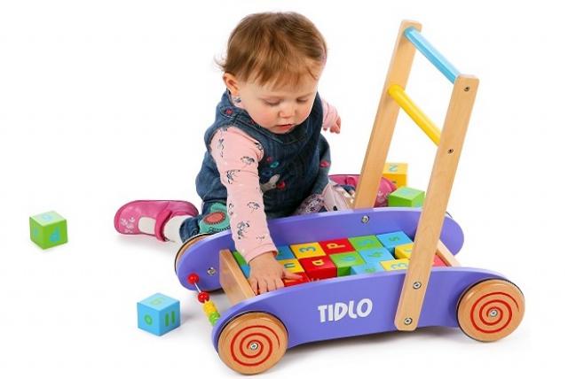 bé chơi với các khối đồ gỗ trong xe đẩy