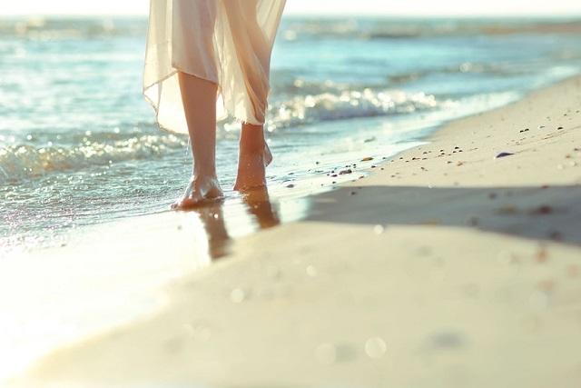 cô gái đi bộ trên biển