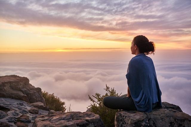 cô gái ngồi trên núi